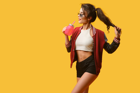 Young glamour woman holding hair and pink drinking jar on yellow background. Stock Photo