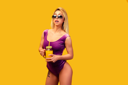Side view of confident blond in sunglasses and pink bodysuit with tattoo on hip drinking refreshing cocktail on orange . Stock Photo