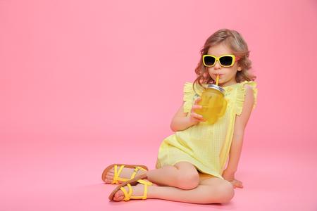 Niña bonita en vestido y gafas de sol sentado en rosa con tarro de cristal de cóctel escalofriante.