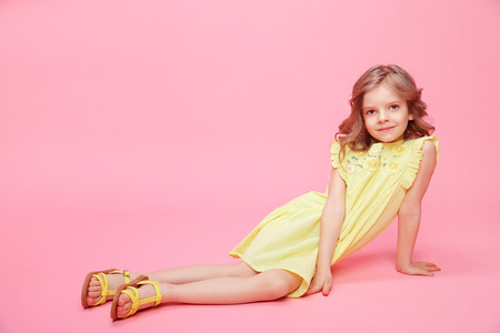 Little adorable model in summer yellow dress and sandals posing on pink backdrop in studio. 免版税图像
