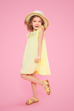 Expressive Charming girl in yellow dress and sandals shouting on pink background. 版權商用圖片 - 100151783