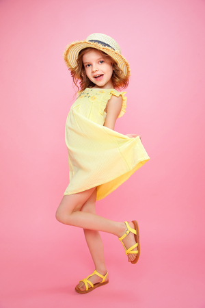 Expressive Charming girl in yellow dress and sandals shouting on pink background. Reklamní fotografie - 100149761