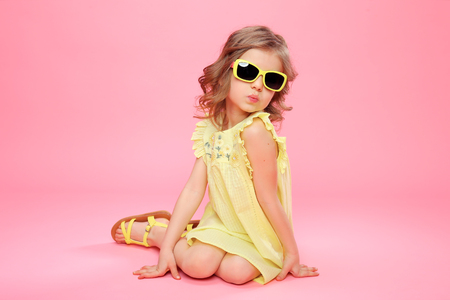 Young little girl in yellow dress and sunglasses sitting on pink background in studio. Standard-Bild