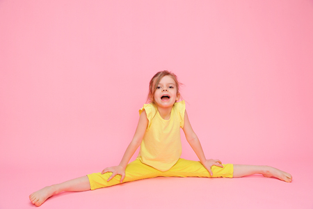 Little charming girl in yellow outfit doing splits while sitting on pink backdrop looking expressively at camera. Stockfoto