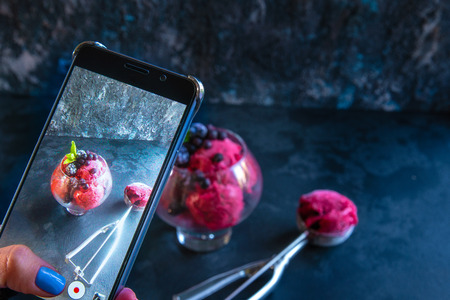 woman hand doing photo of fruit and berry ice cream in a large beautiful glass decorated with leaves of mint and scoop on black stone background by mobile phone. copy, text space