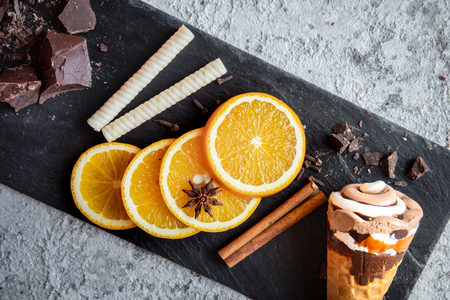 Delicious chocolate and vanilla combo ice cream garnished with fresh orange slices, waffle sticks, cinnamon, bad apple, pieces of chocolate put on shale, white stone backdrop.