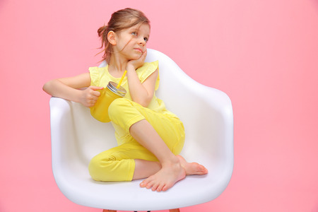 Charming little girl in yellow sitting in chair and daydreaming holding glass with lemonade and straw on pink background. 스톡 콘텐츠