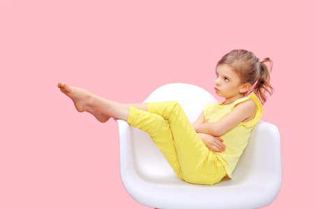 Dreaming Stylish little girl in yellow clothes sitting and posing in chair on pink background.