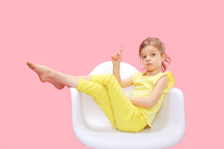 Charming little confident girl in yellow sitting on chair and holding finger up on pink background.