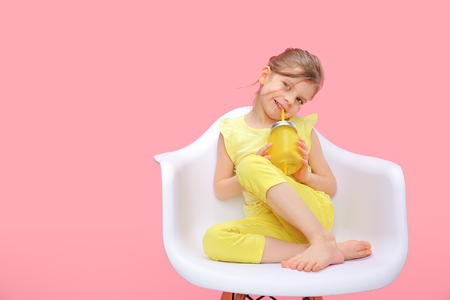 Charming little girl in yellow sitting in chair and smiling holding glass with lemonade and straw on pink background.