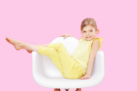 Stylish little girl in yellow clothes sitting and posing in chair on pink background.