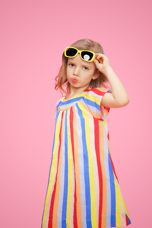 Wonderful little girl in dress and sunglasses sulking lips looking unhappy at camera on pink background.