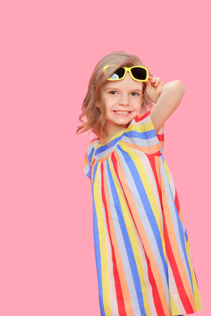 Lovely girl wearing striped colorful dress and sunglasses posing confidently on pink.
