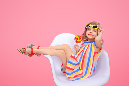 Charming trendy little girl in striped dress and sunglasses holding bright lollipop looking at camera smiling on pink background.
