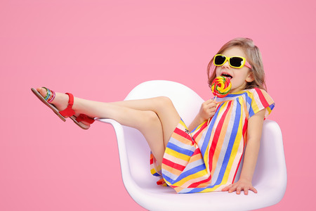 Trendy little model wearing multicolored striped dress with sunglasses and licking swirl lollipop.