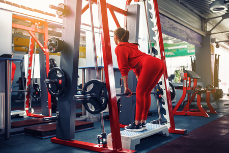 Athletic young woman doing deadlift exercise in the smith machine. Smith rack machine in modern fitness center.