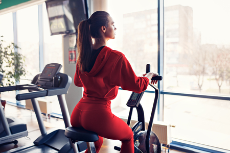Fit young woman using exercise bike at the gym. Fitness female using air bike for cardio workout at gym.