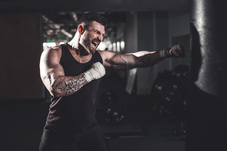 Bearded Male boxer training with punching bag in dark sports hall. Young tattoed boxer training on punching bag. Male boxer as exercise for the big fight. Boxer hits punching bag. Stock fotó