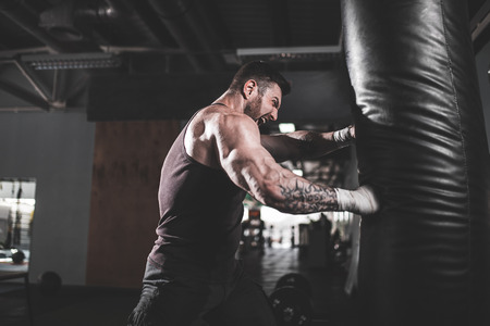 Bearded Male boxer training with punching bag in dark sports hall. Young tattoed boxer training on punching bag. Male boxer as exercise for the big fight. Boxer hits punching bag. 版權商用圖片 - 100559899