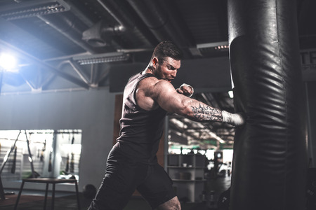 Bearded Male boxer training with punching bag in dark sports hall. Young tattoed boxer training on punching bag. Male boxer as exercise for the big fight. Cool tone. Stock fotó