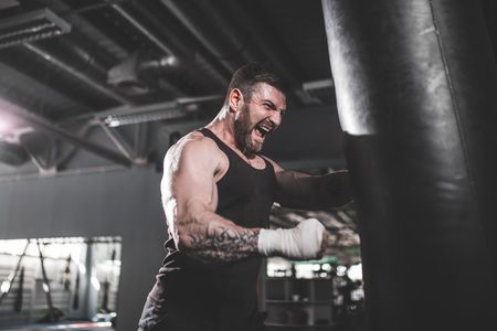 Bearded Male boxer training with punching bag in dark sports hall. Young tattoed boxer training on punching bag. Male boxer as exercise for the big fight. Boxer hits punching bag. 版權商用圖片 - 100559904