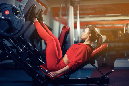Woman doing fitness training on a leg extension push machine with weights in a gym Stock Photo