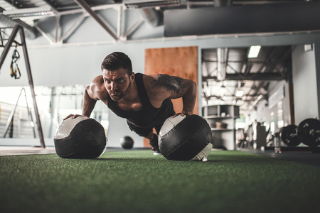Plank it. Confident bearded, tattoed muscled man wearing sport wear and doing plank position on gym balls while exercising in gym. Stock Photo