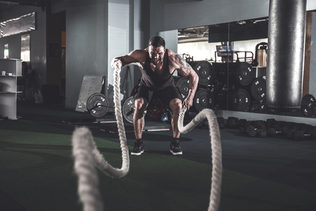 Muscular powerful aggressive man working out with rope in functional training fitness gym Stok Fotoğraf - 100560251