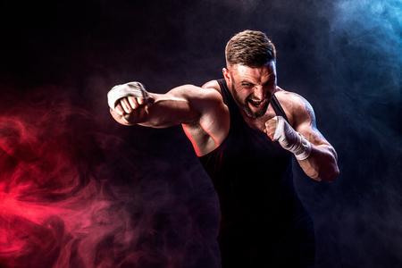 Concepto de deporte. Deportista boxeador de muay thai peleando sobre fondo negro con humo. Copie el espacio.