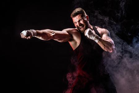 Concepto de deporte. Deportista boxeador de muay thai peleando sobre fondo negro con humo. Copie el espacio. Foto de archivo