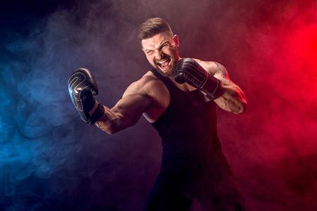 Concetto di sport. Sportivo muay thai boxer combattendo su sfondo nero con fumo. Copia spazio.