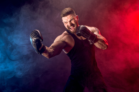 Sportkonzept. Sportler Muay Thai Boxer, der auf schwarzem Hintergrund mit Rauch kämpft. Speicherplatz kopieren.