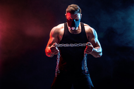 Portrait of muscular sportsman in Training Mask tearing metal chain.Black background with blue, red smoke Imagens