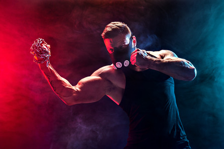 Serious muscular fighter in Training Mask doing the punch with the chains braided over his fist in smoke Stock Photo