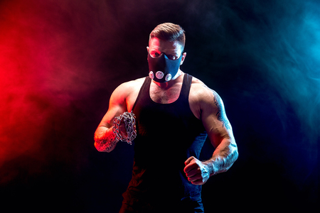 Serious muscular fighter in Training Mask with the chains braided over his fist in smoke