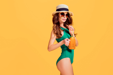 Beautiful young woman in emerald swimwear and straw hat holding jug with cold beverage while standing on yellow background. 版權商用圖片