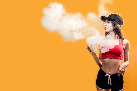 Attractive glamour woman standing and vaping on yellow background. Stock Photo