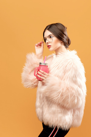 Glamour young woman with pink drinking jar looking away on yellow background.