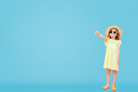 Adorable trendy little model wearing summer dress with hat and sunglasses standing on blue backdrop and pointing on empty space.