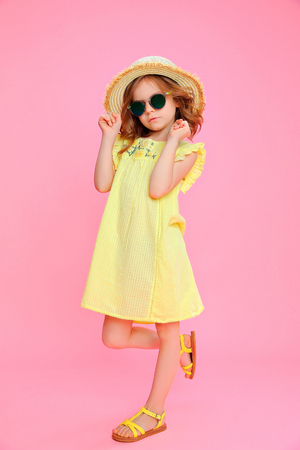Trendy curly girl in dress and sunglasses wearing straw hat posing on pink. Standard-Bild - 101741474