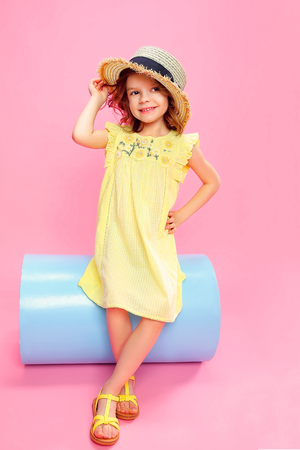 Adorable little girl in yellow light dress and sandals wearing straw hat posing on pink background. 免版税图像