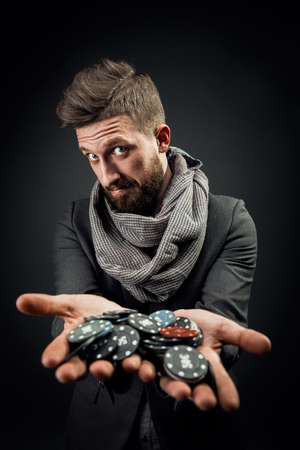 bearded stylish young handsome man holding chips in his hands for the casino and looking at the camera emotionally. dark studio background Banco de Imagens
