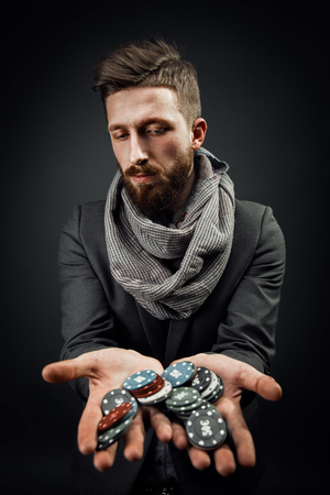 bearded stylish young handsome man holding chips in his hands for the casino and looking at the camera emotionally. dark studio background Reklamní fotografie - 101741510