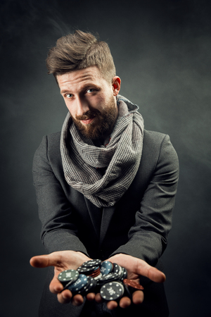 bearded stylish young handsome man holding chips in his hands for the casino and looking at the camera emotionally. dark studio background Zdjęcie Seryjne