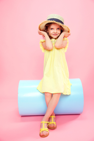 Adorable little girl in yellow light dress and sandals wearing straw hat posing on pink background. Stock Photo