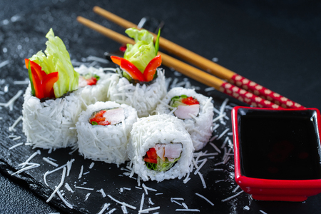 Sushi roll Caesar is sprinkled with parmesan cheese on a black slate plate. Made from smoked chicken fillet, iceberg salad leaf, Bulgarian pepper, Parmesan. Traditional Japanese dish. Stock Photo