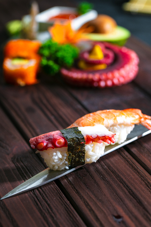 Sushi Set. Different sashimi, sushi and rolls with octopus on knife Stock Photo