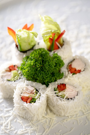 Sushi roll Caesar is sprinkled with parmesan cheese on white plate. Made from smoked chicken fillet, iceberg salad leaf, Bulgarian pepper, Parmesan. Traditional Japanese dish.
