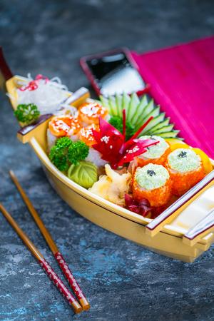 Various kinds of sushi food served decorative boat on black stone Stock Photo