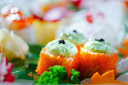 A lot of sushi rolls with different fillings. Shot of cooked classic Japanese food served on ice in a huge wooden bowl. Background image